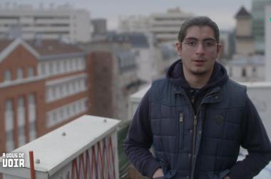 Idriss, avec luettes et cheveux attachés sur un balcon de face