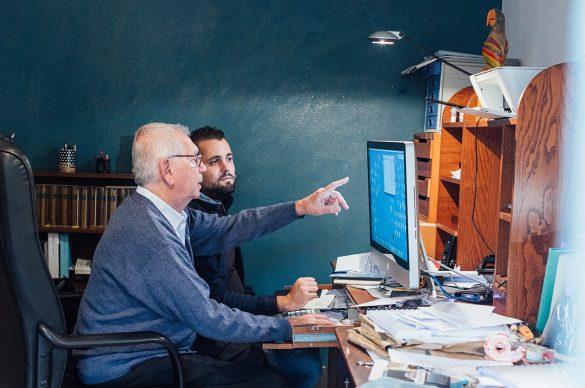Un auxiliaire de vie et une personne malvoyante devant un écran d'ordinateur